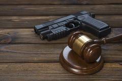 一杆枪和一位锤子法官木纹理桌的背景的 免版税图库摄影