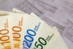 一束以色列新的锡克尔钞票在手上在票据背景 免版税库存图片