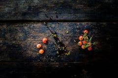 一束在老黑暗的木地板上的新鲜的红色蕃茄 库存图片