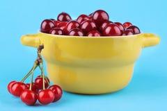 一束成熟,新鲜的樱桃用在一个黄色碗的一棵樱桃在明亮的蓝纸背景 免版税库存图片