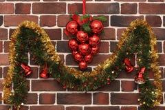 一束红色球和有圣诞节铃声的一本诗歌选在砖墙上 库存图片