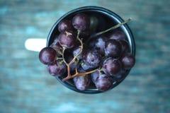 一束葡萄在一个白色杯子的在木绿色背景 免版税库存照片