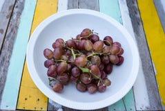 一束葡萄在一个白色碗的 库存图片