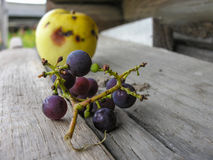 一束葡萄的细节和下落的苹果 免版税库存图片