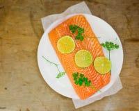 一条三文鱼的新鲜,粗暴内圆角与切片的石灰和绿色 库存图片