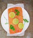 一条三文鱼的新鲜,粗暴内圆角与切片的石灰和绿色 免版税库存图片