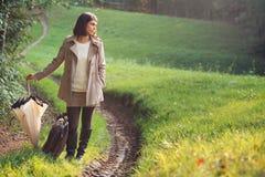一条乡下公路的端庄的妇女带着手提箱 图库摄影