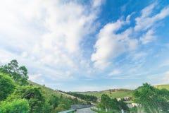一条乡下公路的美好的风景视图有蓝天bac的 免版税库存图片