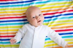 一条五颜六色的毯子的逗人喜爱的婴孩 库存图片