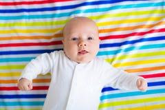 一条五颜六色的毯子的逗人喜爱的婴孩 免版税图库摄影