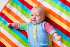 一条五颜六色的毯子的逗人喜爱的婴孩 免版税库存照片