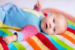 一条五颜六色的毯子的逗人喜爱的婴孩 免版税库存图片