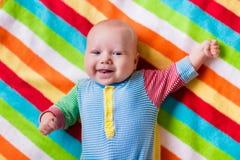 一条五颜六色的毯子的逗人喜爱的婴孩 库存照片