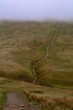 一条人行道/路在小山在雾,笔y爱好者峰顶,布雷肯比肯斯山,威尔士,英国 库存照片
