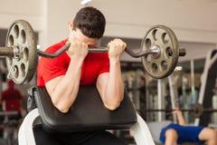 一条传教者长凳的年轻人在健身房 免版税库存照片
