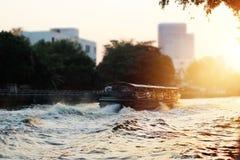 一条传统小船在日落背景的河城市 库存照片