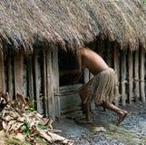一条传统裙子的妇女在小屋掩藏。 免版税图库摄影