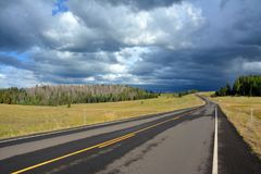 一条偏僻的双线道路带领入黑暗和风雨如磐的天际 免版税库存图片