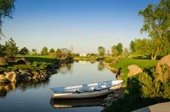 一条偏僻的小船沿湖航行在美好的绿色领域之间 免版税库存照片