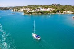 一条偏僻的白色游艇在公海航行到与小白色房子的美丽如画的岸, Menorca,西班牙,顶视图 库存图片