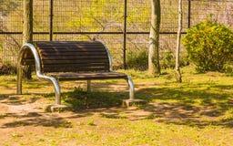 一条偏僻的长凳在一个空的公园 免版税库存照片