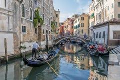 一条典型的威尼斯式运河的美丽的景色,威尼斯,意大利,有在长平底船的一对夫妇的,拍照片和做录影 免版税库存图片