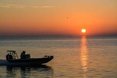 一条加速的小船的剪影在坦帕湾的日出的在圣彼德堡,佛罗里达 库存图片