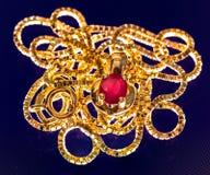 一条可爱的金黄项链的Macrophoto与红宝石石头的在偏光 免版税库存图片
