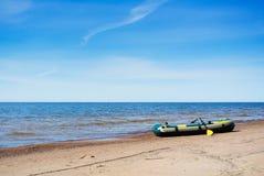 一条可膨胀的小船在波罗的海海岸的早期的春天早晨  图库摄影