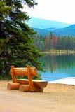 一条土气长凳坐在山的镇静湖岸 库存照片