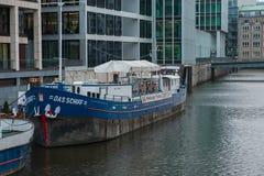 一条大小船在停车场的一个船坞站立在企业处所旁边 免版税图库摄影