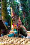 一条大绿色纳卡人蛇的雕象与金黄飞翅的 库存照片