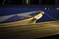 一条小木小船停放在船坞或码头在晚上 夜摄影用蓝色光滑的水 免版税库存图片