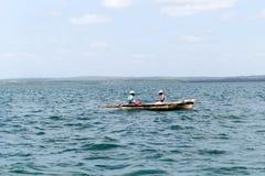 一条小木小船的两位地方渔夫在印度洋,坦桑尼亚 免版税库存图片