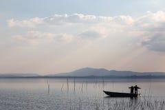 一条小的小船的两位渔夫有一个捕鱼网的,与beautifu 免版税库存照片