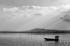 一条小的小船的两位渔夫有捕鱼网和遥远的su的 库存照片