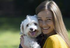 一条小的白色狗的容忍的微笑的女孩 在她的面孔的大微笑 免版税库存照片