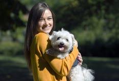 一条小的白色狗的容忍的微笑的女孩 库存照片