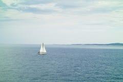一条小的航行游艇在海运 库存照片