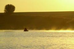 一条小船传染性的鱼的渔夫及早在金黄雾 库存照片