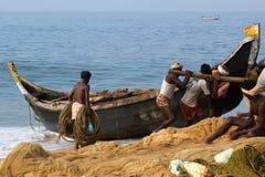 一条小船传染性的鱼的渔夫在海洋,南印度 免版税库存照片