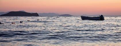 一条小船和一个海岛日落的 免版税库存照片