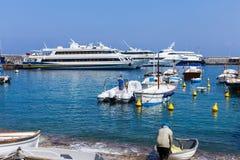 一条小船和一位沿海渔夫的一名船员在小游艇船坞重创的港口,意大利 库存照片