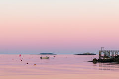 一条小船和龙虾浮体在黄昏的风平浪静 库存图片