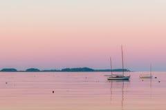 一条小船和龙虾浮体在黄昏的风平浪静 图库摄影