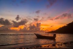 一条小船在日出期间的海 库存图片