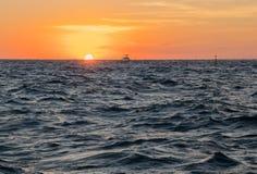 一条小船在日落的三角浪 库存照片