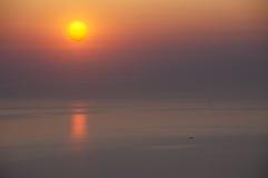 一条小船在朝阳下的海 免版税库存照片