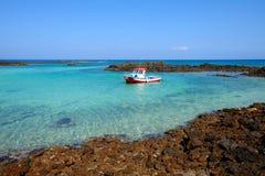 一条小船在海岛罗伯斯,西班牙上的一个盐水湖 免版税库存照片