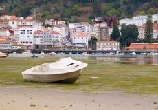 一条小船处于低潮中在Pontedeume 免版税库存照片